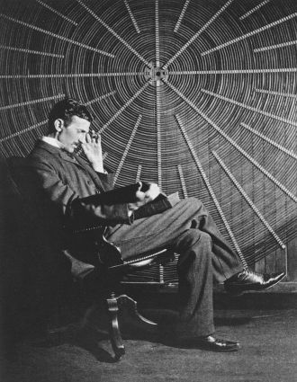 01 Nikola Tesla sits in front of a spiral coil from a high-voltage transformer at his East Houston St New York laboratory in 1896
